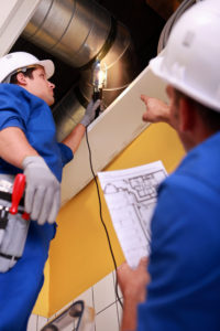 Two workers inspecting ventilation system